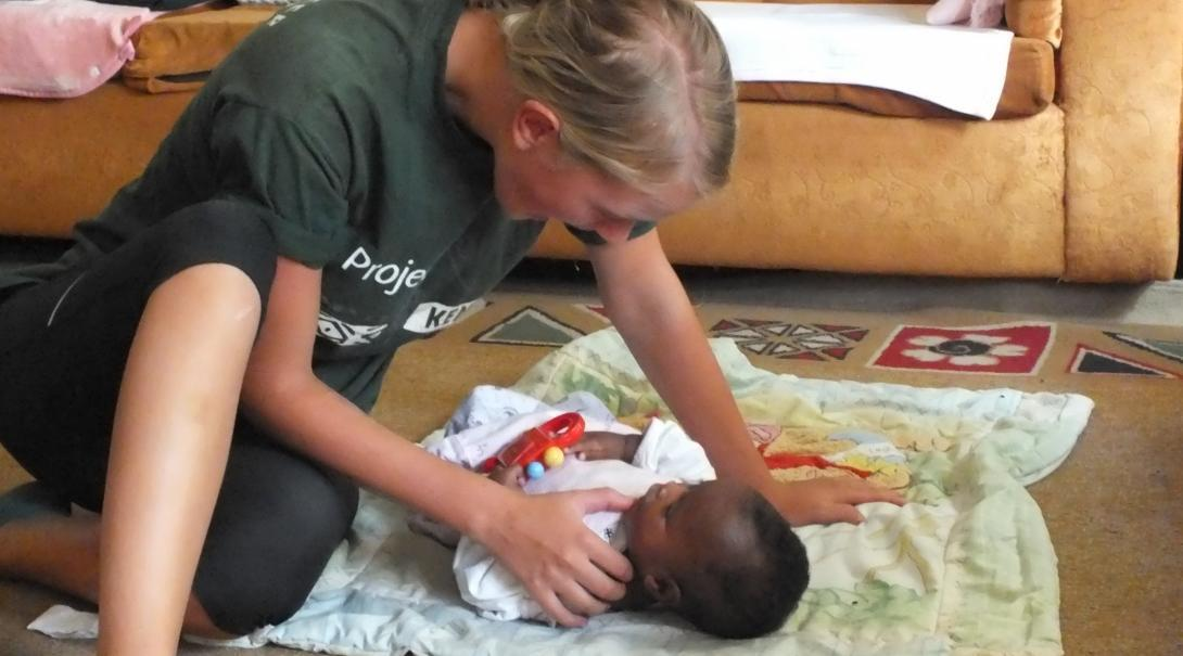A Projects Abroad intern is pictured interacting with a baby whilst on her occupational therapy internship in Kenya.